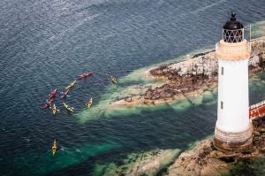 A pod of kayakers exploring the clear waters around Kyleakin Lighthouse. Highlands, Scotland.