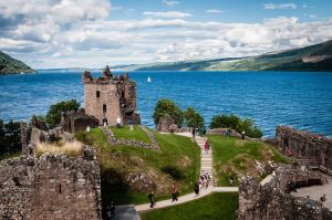 The ruins of Urquhart Castle overlook the deep blue waters of Loch Ness in the Highlands of Scotland.