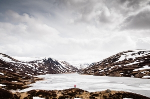Steph standing just above the shoreline of a partially frozen Loch Callater. Invercauld Estate, Cairngorms National Park, Scotland.