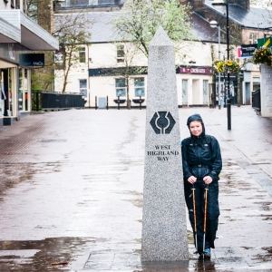 Already soaked with rain, Steph stops for a photo at the obelisk marking the southern starting point - or terminus if coming from the north - of the West Highland Way in Milngavie, Scotland.