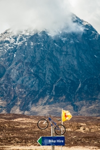 Signage advertising for the Glencoe Mountain Resort with Buachaille Etive More in the background.