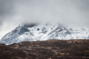 A group of hikers stops at the top of the Devil's Staircase on the West Highland Way as storm clouds close in.