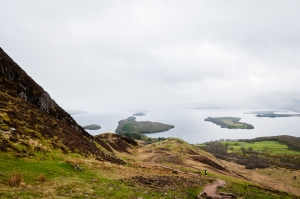 The West Highland Way descends steeply from the flanks of Conic Hill towards Loch Lomond and the village of Balmaha.