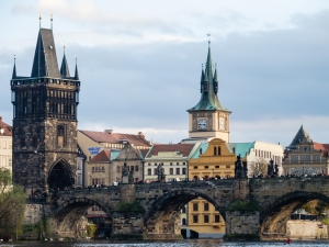 Soft sunset light falls on the Vltava River and Charles Bridge in Prague, Czech Republic.