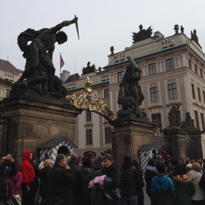People gathered around waiting to witness the changing of the guard ceremony at Prague Castle.